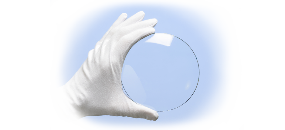 A white gloved hand holding an example of Glass Quarter Wave & Half Wave Retarders | American Polarizers, Inc.